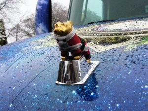 The santa outfit on the hood ornament of the Mack Christmas Tree Truck